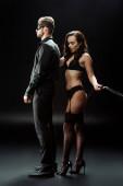 dominante Frau in Unterwäsche hält Prügelpeitsche neben Mann mit Augenbinde auf Schwarz