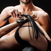 Fotografie abgeschnittene Ansicht eines hemdlosen Mannes mit Peitsche in der Nähe der unterwürfigen Frau isoliert auf schwarz
