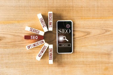 top view of wooden rectangles with concept words of seo and smartphone with seo illustration
