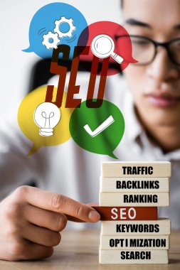 selective focus of asian seo manager holding wooden rectangle with lettering seo and sitting near seo illustration