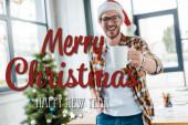 szelektív fókusz boldog szakállas férfi télapó kalap tartó csésze közel karácsonyfa az irodában boldog karácsonyt és boldog új évet illusztráció