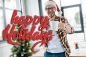 messa a fuoco selettiva delluomo barbuto felice in Santa hat tenendo la tazza vicino albero di Natale in ufficio con illustrazione di festa felice