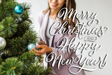 cropped view of businesswoman decorating christmas tree with merry Christmas and happy new year illustration