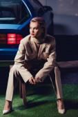 attraktive und stilvolle Frau im Anzug sitzt auf Holzbank in der Nähe von Retro-Auto