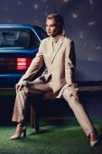 vonzó és elegáns nő öltönyben ül fa padon közel retro autó