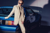 attractive and stylish woman in suit and sunglasses standing near retro car