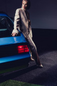 attractive and stylish woman in suit standing near retro car