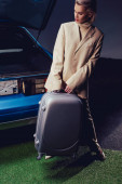 attractive and stylish woman in suit holding suitcase and standing near retro car
