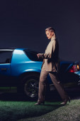 attractive and stylish woman in suit walking near retro car