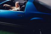 Fotografie vysoký úhel pohledu atraktivní a stylové ženy v obleku sedí v retro autě