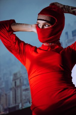 low angle view of stylish woman in red dress and balaclava on city background