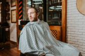 vousatý muž v svlečeném holiči plášti sedí v holičství