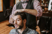 barber styling hair on handsome bearded man