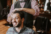 barber styling hair on cheerful bearded man