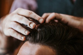 cropped view of barber with black hair pomade on hands styling hair of man