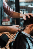 cropped view of barber styling hair of man in barbershop