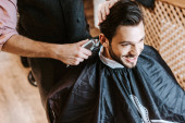 barber holding trimmer while styling hair of happy man in barbershop