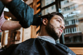 selective focus of barber in latex gloves holding hair comb while styling hair of man