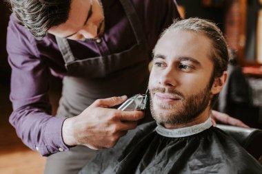 Barber holding trimmer while shaving bearded man stock vector