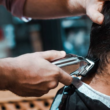 Close up of barber styling hair of man in barbershop stock vector