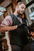 Fotografia tattooed barber in latex gloves holding hair comb and scissors while styling hair of man