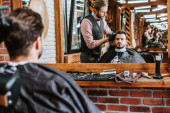 selective focus of handsome barber styling hair of man near mirror in barbershop