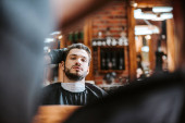 selective focus of barber styling hair of bearded man near mirror in barbershop