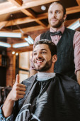 selective focus of happy man showing thumb up near barber