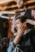 selective focus of handsome man touching hair near barber