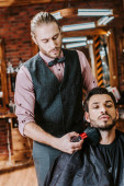 handsome barber holding cosmetic brush near face of bearded man