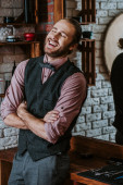 cheerful barber standing with crossed arms and laughing in barbershop