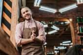 Fotografie selective focus of happy barber in apron standing with clenched hands