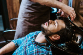 tattooed barber washing hair of bearded man with closed eyes