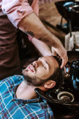Fotografia tattooed barber washing hair of handsome man with closed eyes