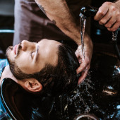 tattooed barber washing wet hair of man in black sink
