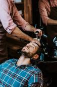 Fényképek tattooed hairdresser washing hair of man in black sink near mirror