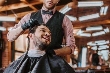 Bearded barber in black latex gloves touching hair of happy man in barbershop stock vector