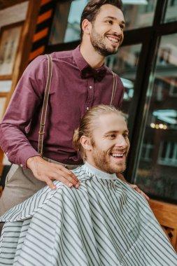happy barber putting hands on shoulders of handsome man in barbershop
