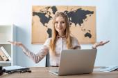 Fotografie lächelndes Reisebüro zeigt Willkommensgeste, während es neben Laptop sitzt