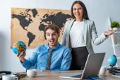 attraktives Reisebüro zeigt Willkommensgeste, während es neben lächelndem Kollegen mit Globus steht