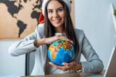 Fotografie glückliches Reisebüro mit Globus in der Hand und lächelnd in die Kamera