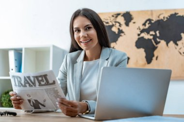attractive travel agent holding travel newspaper and looking at camera