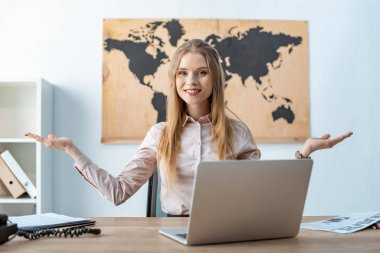 smiling travel agent showing welcome gesture while sitting near laptop