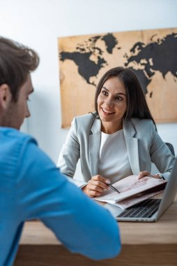 smiling travel agent pointing with pen at map while talking to client