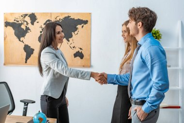 smiling travel agent shaking hands with happy man standing near girlfriend