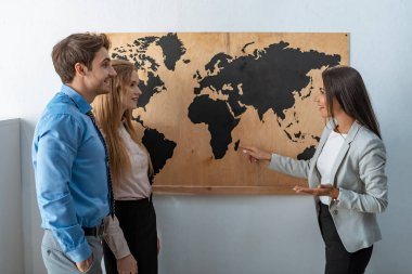 smiling travel agent pointing with finger at map on wall near couple of tourists