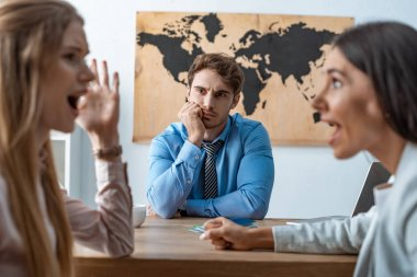 selective focus of quarreling couple near bored travel agent
