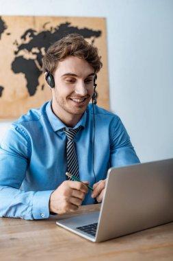smiling travel agent in headset looking at laptop