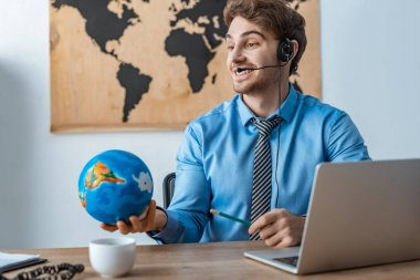 smiling travel agent holding globe while sitting at workplace