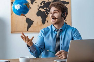cheerful travel agent throwing up globe while sitting at workplace